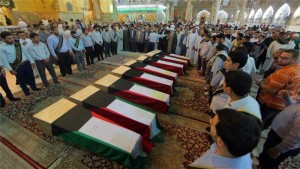 MOURNING — Kuwaiti Shias line up behind the coffins of some of those killed in the bombing.