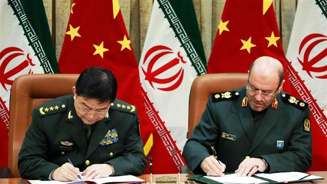 MYSTERY PACT — Chinese Defense Minister Chang Wanquan (left) and Iranian Defense Minister Hossain Dehqan sign an agreement on military cooperation Monday in Tehran.  No one said what kind of cooperation the agreement provides for.